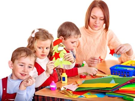 maestra preescolar: Kinder maestro con los niños del grupo. Aislado en blanco. Foto de archivo