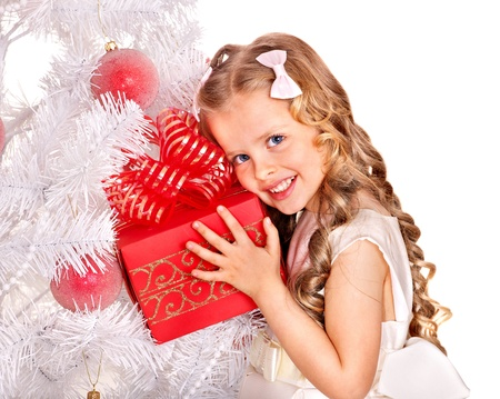 Child with gift box near white Christmas tree. Isolated. Stock Photo - 11439578