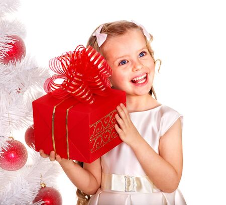 Child with gift box near white Christmas tree.  Isolated. photo