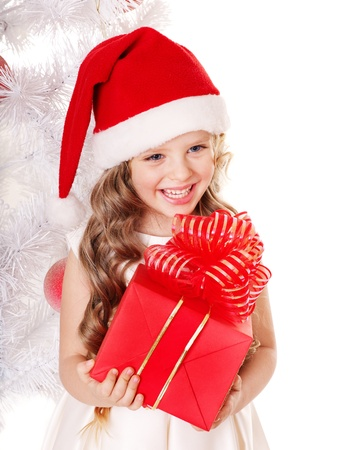 Child in Santa hat with gift box near white Christmas tree. Isolated. photo