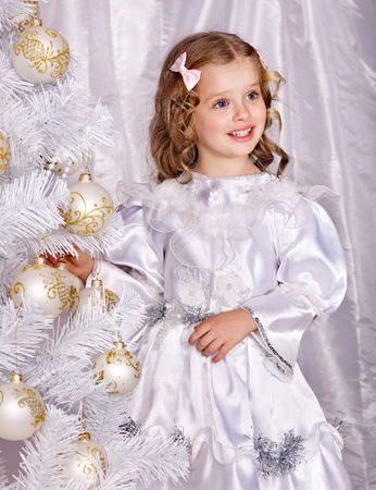 Child holding gift box and decorate white Christmas tree.  photo
