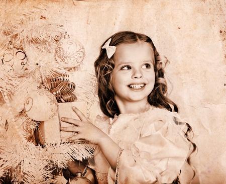 Enfant avec boîte-cadeau blanche près de sapin de Noël. Vieille photo sépia.