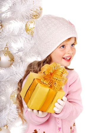 Child in hat and mittens holding gold  gift box near white Christmas tree. Isolated. photo