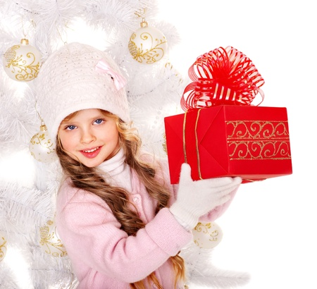 Child in hat and mittens holding red  gift box near white Christmas tree. Isolated. photo