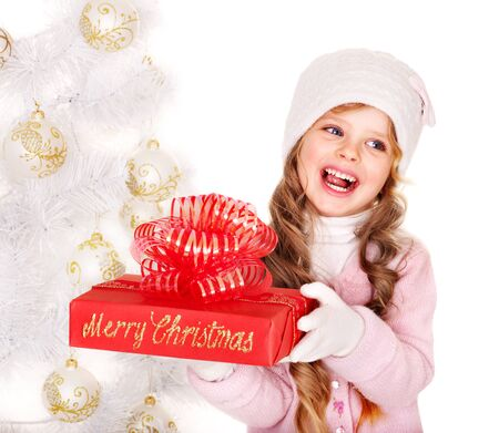 red gift box: Child in hat and mittens holding red  gift box near white Christmas tree. Isolated. Stock Photo