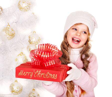 the mittens: Ni�o con sombrero y guantes de la celebraci�n de caja de regalo de color rojo cerca del blanco del �rbol de Navidad. Aislados. Foto de archivo