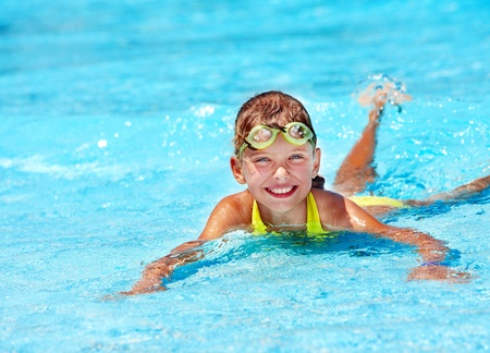 armbands: Little girl in swimming pool. Summer outdoor.