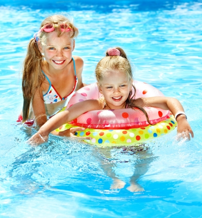 swimming pool float: Children sitting on inflatable ring in swimming pool. Stock Photo