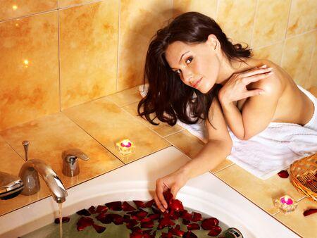 woman in bath: Woman sitting on edge of bath tub.