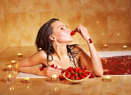 Woman eting strawberry in bathroom. photo