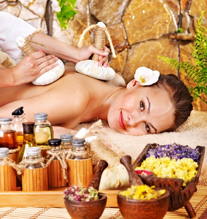 parlour: Woman getting thai herbal compress massage in spa.