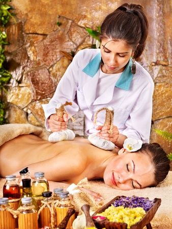 massage herbal: Young woman getting massage in spa.