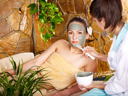 mud woman: Beautiful girl having clay body mask apply by beautician.