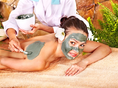 body mask: Beautiful girl having clay body mask apply by beautician.