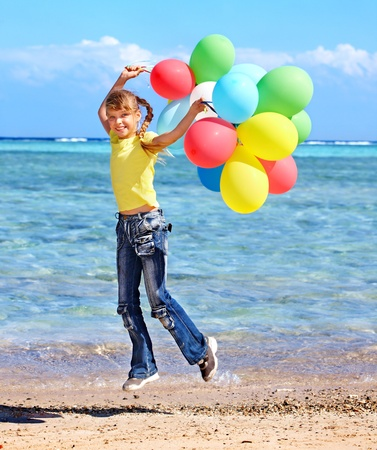 red jeans: little girl playing with balloons at the beach. Stock Photo