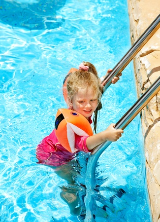 armbands: Child with armbands in swimming pool. Summer outdoor.