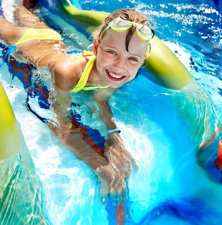 child in bikini: Child on water slide at aquapark. Summer holiday.