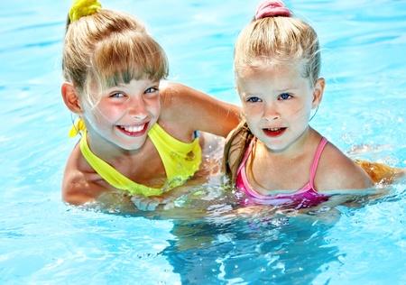 Children in swimming pool. Summer outdoor. photo