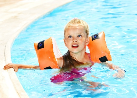 Child with armbands in swimming pool. Summer outdoor. photo