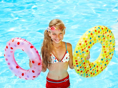 float tube: Child sitting on inflatable ring in swimming pool.