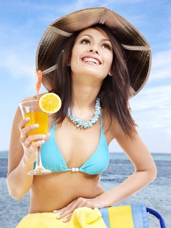Girl in bikini drink juice through a straw. photo