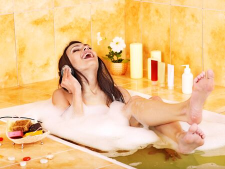 Woman listening to music in bubble  bath. photo