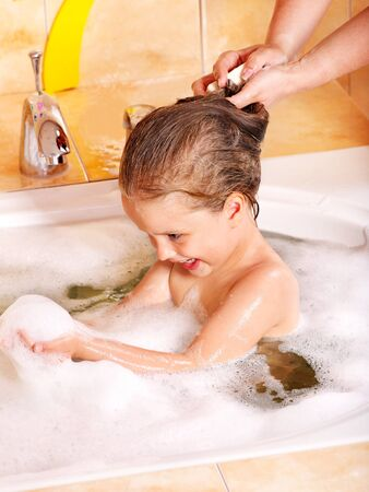 Child washing hair in bubble bath. photo