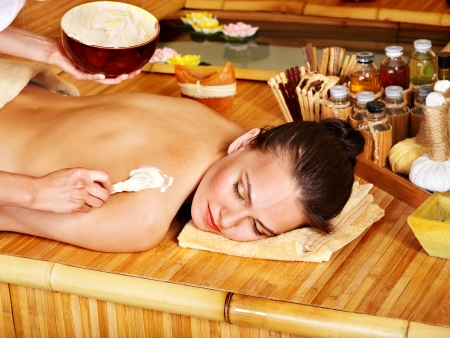 health resort treatment: Young woman getting salt massage.