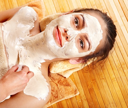 Beautiful girl having clay facial mask and body apply by beautician. photo