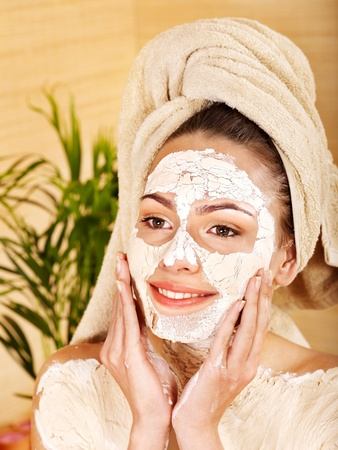 parlour: Beautiful girl having clay facial and body mask apply by beautician. Stock Photo