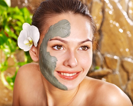 mujer maquillandose: Hermosa niña con máscara de barro facial aplicar por esteticista.