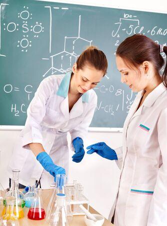 examenes de laboratorio: Mujer estudiante de química con frasco en el aula. Foto de archivo
