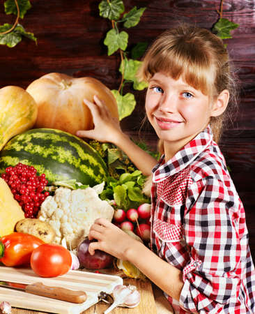 Little girl with vegetable on kitchen. photo