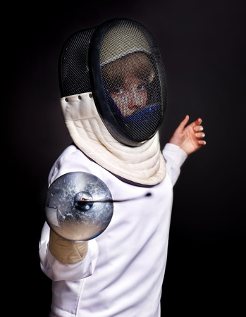 Child epee fencing lunge. Dark background. photo