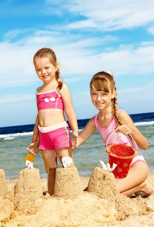 sandcastles: Little girl  playing on  beach.