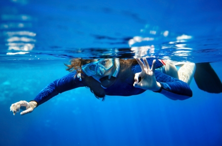 Scuba diver young woman in  blue water. photo