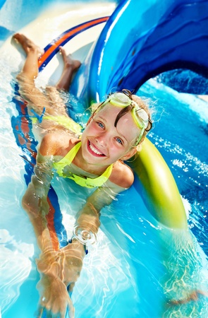 Child on water slide at aquapark. Summer holiday. Stock Photo - 12341227