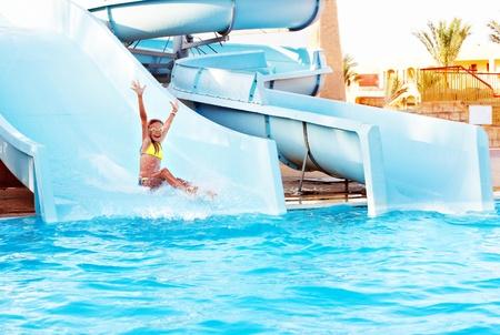 Child on water slide at aquapark. Summer holiday. Stock Photo
