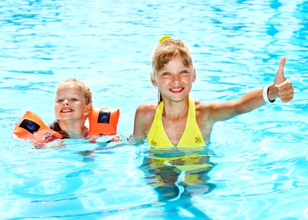 Child with armbands in swimming pool. Summer outdoor. Stock Photo - 12341226