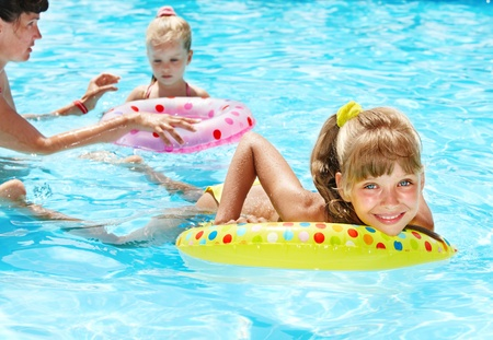 Happy family with children sitting on inflatable ring in swimming pool. photo
