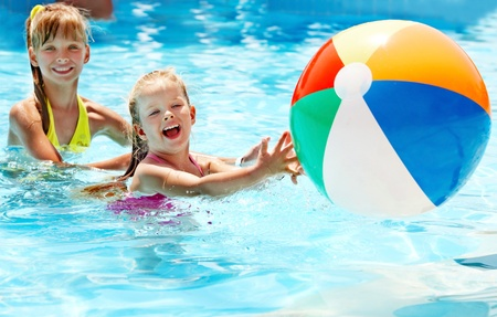 pool ball: Little girl  swimming in pool. Stock Photo