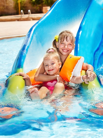 water wings: Children on water slide at aquapark. Summer holiday. Stock Photo