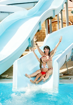 Child with mother on water slide at aquapark. Summer holiday.
