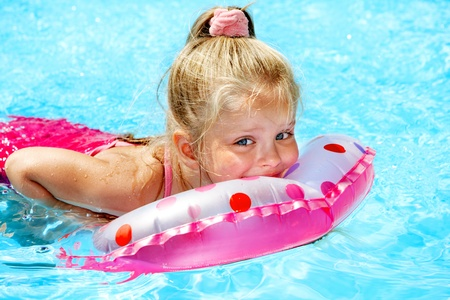 Child sitting on inflatable ring in swimming pool. Stock Photo - 12341012