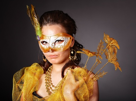 Beautiful young woman  in carnival costume with gold mask. photo