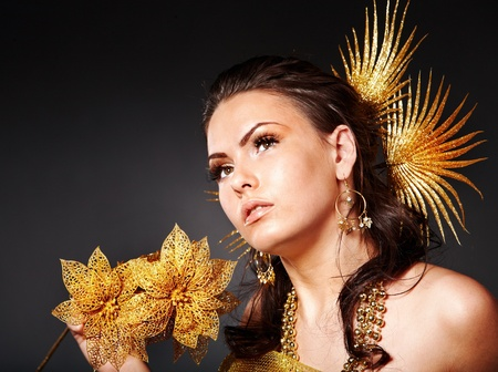 Beautiful young woman  in carnival costume with gold flower. photo