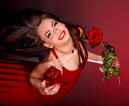 Young woman with flower and gift box. Valentine's day. photo