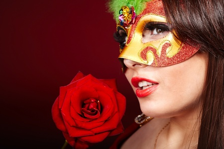 Beautiful girl with red flower rose and mask. photo