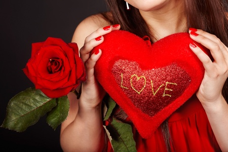 hands holding heart: Girl with  heart and flower rose on red  background.  Valentines day.