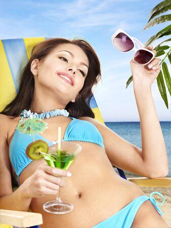 Girl in bikini at beach drink juice through a straw. photo